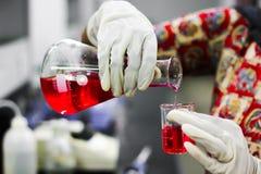 Лить красную жидкость от стеклянной конической склянки к стеклянному beaker с gloved рукой в химической лаборатории стоковая фотография
