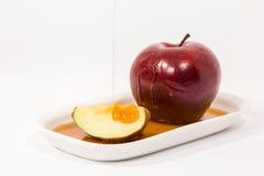 Лить мед на красном куске яблока и яблока красного цвета на белых wi плиты Стоковое Изображение RF
