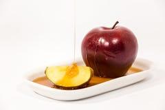 Лить мед на красном куске яблока и яблока красного цвета на белых wi плиты Стоковые Изображения RF