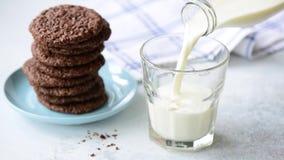 Лить молоко в стекло Молоко и печенья акции видеоматериалы