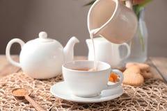 Лить молоко в чашку с ароматичным чаем на плетеной циновке стоковое изображение