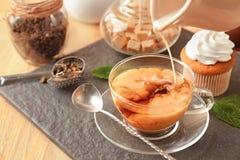 Лить молоко в чашку с ароматичным чаем на плите шифера стоковое изображение