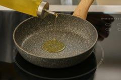 Лить оливкового масла в сковороду на плите стоковые фото
