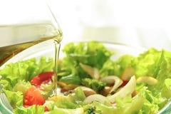 Лить оливкового масла в шар со здоровым салатом, крупный план стоковое фото