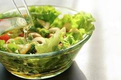 Лить оливкового масла в шар со здоровым салатом стоковые изображения rf