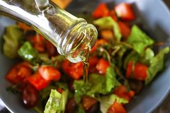 Лить оливкового масла в шар с салатом свежего овоща, крупный план стоковые фото