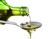 Лить оливкового масла от бутылки в ложку на белой предпосылке стоковая фотография rf