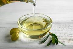 Лить оливкового масла от бутылки в стеклянный шар на деревянном столе стоковое изображение