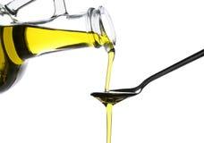 Лить оливкового масла от стеклянного кувшина в ложку на белой предпосылке стоковые фотографии rf