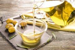 Лить оливкового масла от стеклянного кувшина в шар на таблице стоковая фотография