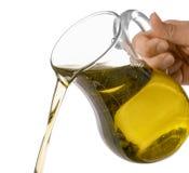 Лить оливкового масла от стеклянного кувшина на белой предпосылке стоковое изображение