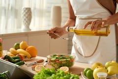 Лить оливковое масло в салат стоковая фотография rf