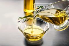 Лить оливковое масло в стеклянный шар на таблице, крупном плане стоковая фотография rf