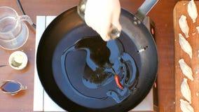 Лить оливковое масло над лотком Стоковые Фото