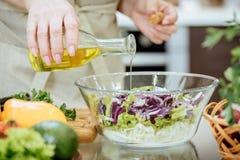 Лить оливковое масло на свеже сделанном салате стоковые фотографии rf