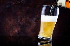 Лить пиво в стекло на темной деревянной предпосылке стоковое изображение
