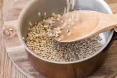 Лить рис всего зерна коричневый в медный бак на деревянной ложке стоковое изображение