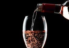 Лить розовое розовое вино от бутылки к стеклу на черноте стоковое фото rf