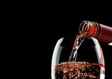 Лить розовое розовое вино от бутылки к стеклу на черноте стоковые фотографии rf