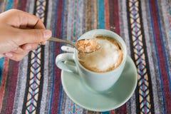 Лить сахар на кофейной чашке Стоковые Фотографии RF