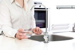 Лить свежая вода от фильтра озона в стекло женщиной внутри Стоковое Изображение