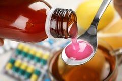 Лить сироп кашля от бутылки в ложку стоковое изображение