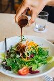 Лить соус в свежий салат стоковые фотографии rf
