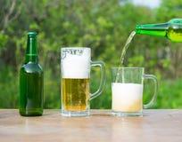 Лить стекла пива от бутылки на зеленой предпосылке Стоковые Фото
