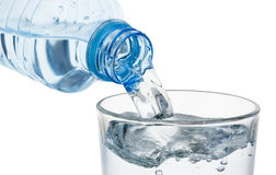 Лить стекло воды от пластичной изолированной бутылки Стоковое Изображение RF