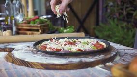Лить сыр на сырцовой пицце пока подготовка на кухне пиццерии Pizzaillo делая пиццу с сыром, томатами и видеоматериал