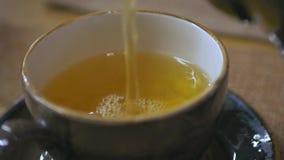 Лить чай от чайника в винтажное керамическое чашка сток-видео