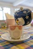 Лить чай от чайника к чашке Стоковые Изображения