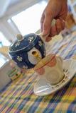 Лить чай от чайника к чашке Стоковая Фотография RF