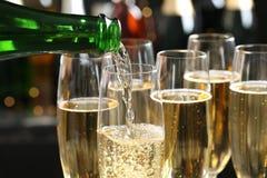 Лить шампанское в стекла на запачканной предпосылке стоковые фотографии rf