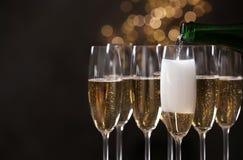Лить шампанское в стекла на запачканной предпосылке, крупном плане стоковая фотография rf