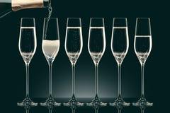 Лить шампанское от бутылки в 6 прозрачных стекел Стоковые Фотографии RF