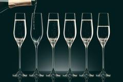 Лить шампанское от бутылки в 6 прозрачных стекел Стоковое фото RF