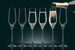 Лить шампанское от бутылки в 6 прозрачных стекел Стоковая Фотография RF