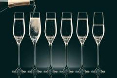 Лить шампанское от бутылки в 6 прозрачных стекел Стоковое Фото