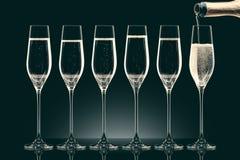 Лить шампанское от бутылки в 6 прозрачных стекел Стоковое Изображение RF