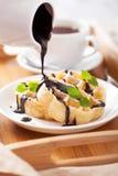 Лить шоколад над бельгийскими waffles для завтрака Стоковые Фото