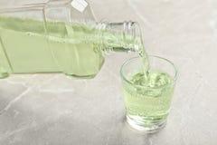 Лить mouthwash в стекле на светлой предпосылке стоковое фото