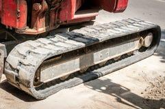 Лицевая часть малого экскаватора бульдозера движенца земли с следами на строительной площадке улицы подготовила для работы Стоковая Фотография RF