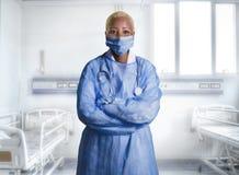 Лицевой щиток гермошлема и синь привлекательного и уверенного черного Афро-американского доктора медицины нося scrubs стоять корп стоковая фотография