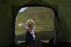 Личная перспектива мужского туриста в шатре в швейцарских горных вершинах с молодой женщиной делая форму сердца руки перед им стоковая фотография rf