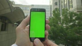 Личная перспектива человека используя smartphone Зелен-экрана вне офиса акции видеоматериалы