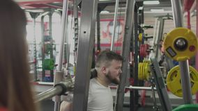 Личная тренировка с инструктором девушки для человека с большим брюшком в спортзале Толстый брюзгливый парень вместе с частным тр сток-видео