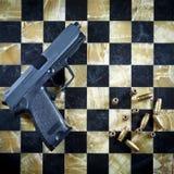 Личное огнестрельное оружие и пули на Checkered таблице шахмат Стоковые Изображения