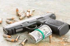 Личное огнестрельное оружие с деньгами и разбросанными пулями Стоковое Изображение RF