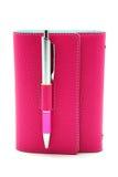 Личный организатор в розовом цвете с ручкой шариковой авторучки на белой предпосылке Стоковое фото RF